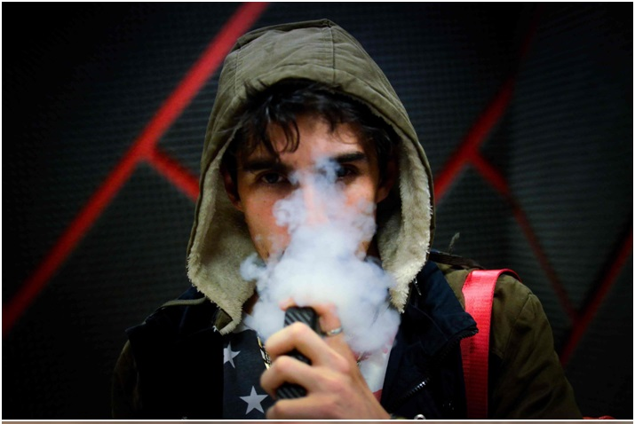 Medium close up of man in hoodie with face obscured by vapour cloud.